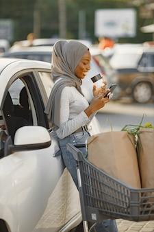 Используя смартфон во время ожидания. женщина африканской национальности на зарядной станции электромобилей в дневное время. совершенно новый автомобиль.
