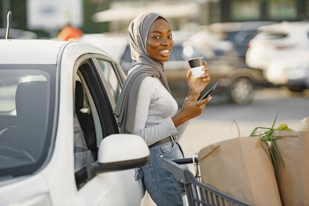 기다리는 동안 스마트폰을 사용합니다. 낮에 전기 자동차 충전소에 아프리카 민족 여자.