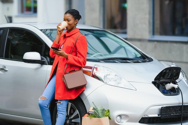 待っている間にスマートフォンを使用します。昼間の電気自動車充電ステーションの女性。真新しい車。