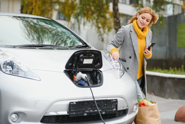 待っている間にスマートフォンを使用する。昼間の電気自動車充電ステーションの女性