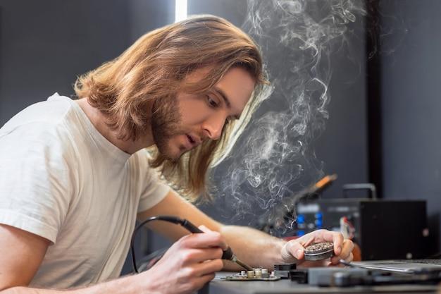 С помощью паяльника. молодой взрослый длинноволосый мужчина с горячим паяльником и коробкой припоя работает, сидя за столом в мастерской