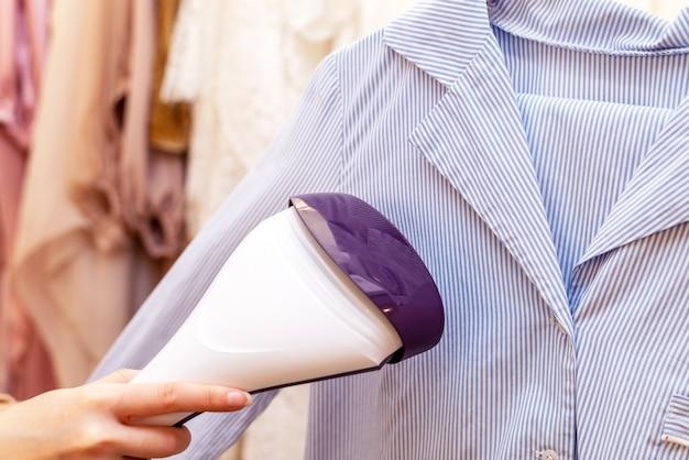 洗濯室でシャツにアイロンをかけるために蒸しアイロンを使用するクローズアップ