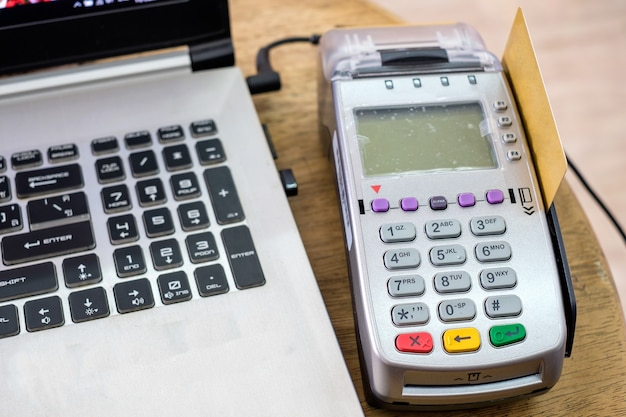 Using swipe credit card on payment terminal with laptop on wood table