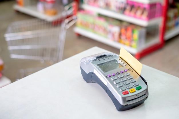슈퍼마켓의 결제 단말기에서 신용 카드를 스와이프하여 사용