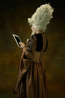 Using tablet to be online. portrait of medieval young woman in brown vintage clothing on dark wall. female model as a duchess, royal person. concept of comparison of eras, modern, fashion.
