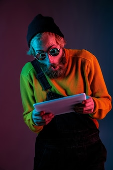 Using tablet, looks shocked. caucasian man's portrait on gradient studio background in neon light. beautiful male model with hipster style. concept of human emotions, facial expression, sales, ad.