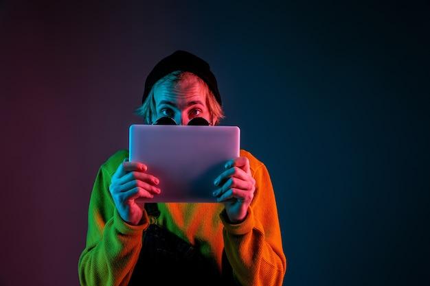 Используя планшет, выглядит шокированным