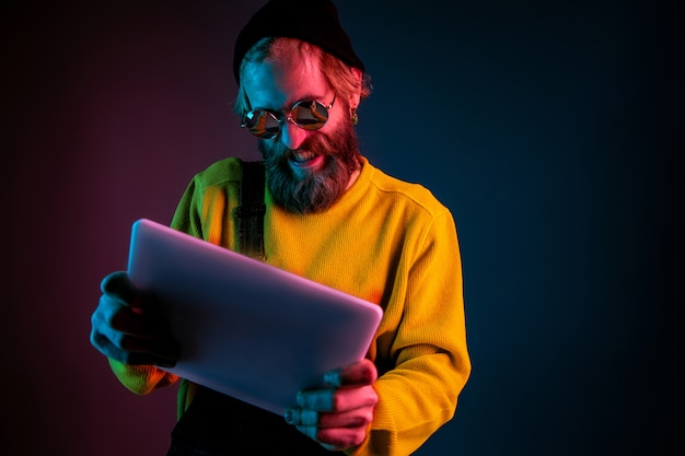 Using tablet, playing game. caucasian man's portrait on gradient  space in neon light