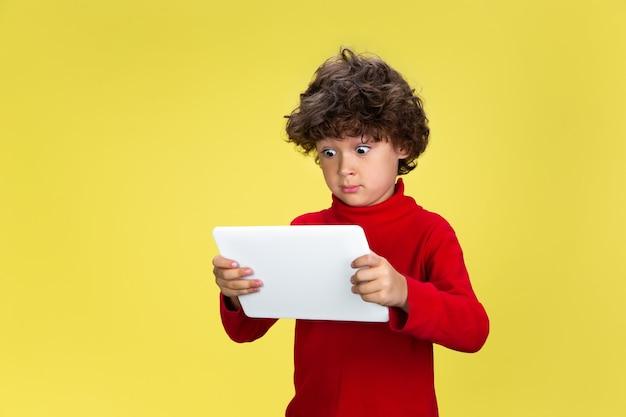 태블릿 사용. 노란색 스튜디오 벽에 빨간 스웨터를 입은 예쁜 곱슬머리 소년의 초상화
