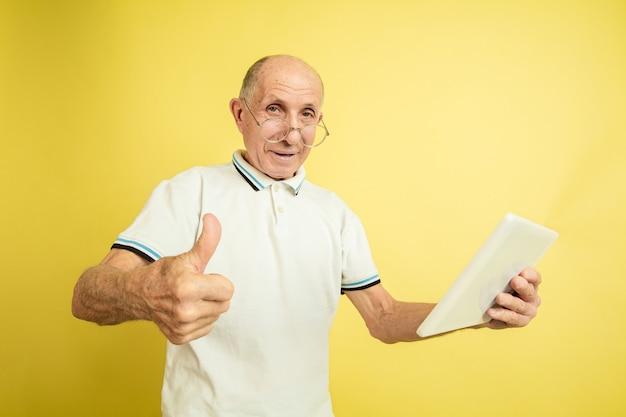 Utilizzando tablet, pollice in su. ritratto dell'uomo maggiore caucasico su sfondo giallo studio. bellissimo modello emotivo maschile. concetto di emozioni umane, espressione facciale, vendite, benessere, annuncio. copyspace.