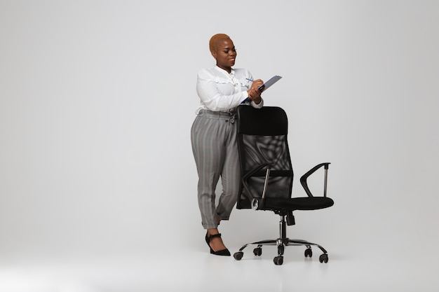 Using tablet. young woman in office attire. bodypositive female character, feminism, loving herself, beauty concept. plus size businesswoman on gray background. boss, beautiful. inclusion, diversity.