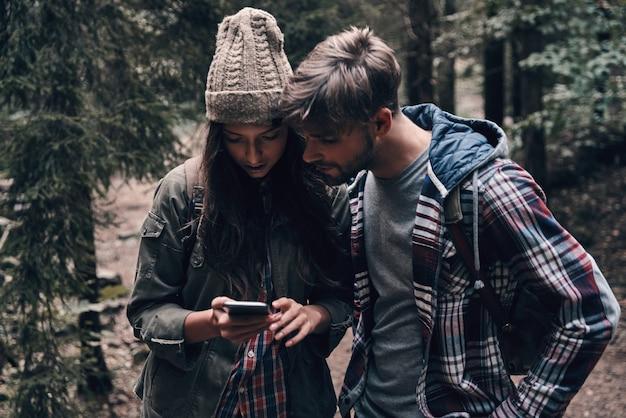Используя технологии. красивая молодая пара, глядя на смартфон во время прогулки вместе в лесу