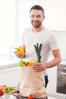 新鮮な野菜を使って食事をしています。キッチンに立って笑っている間、新鮮な野菜でいっぱいの買い物袋を開梱するハンサムな若い男