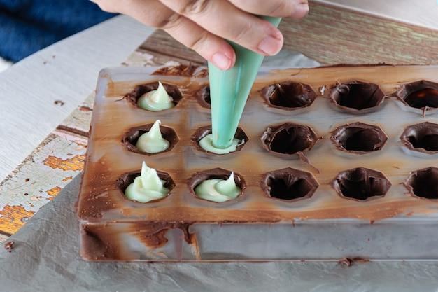 아이싱 노즐을 사용하여 초콜릿 캔디에 녹색 가나슈를 채 웁니다.