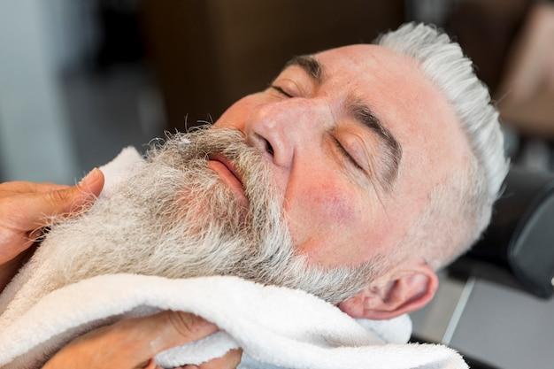 Using towel on beard of aged male in barbershop