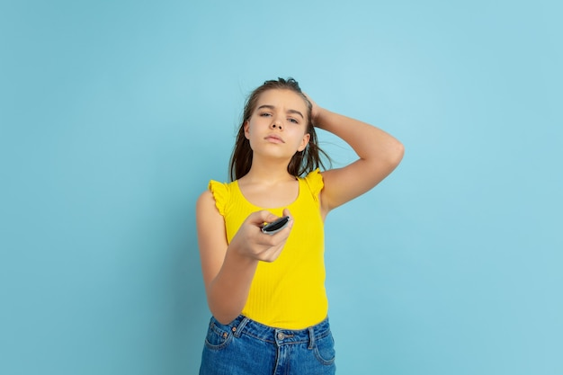 テレビのリモコンを使用する。青い壁に分離された白人の十代の少女の肖像画。カジュアルで美しいロングヘアモデル。人間の感情、顔の表情、販売、広告の概念。コピースペース。かわいく見えます。
