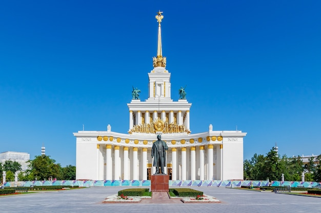 Павильон ссср в парке вднх в москве против памятника владимиру ленину на фоне голубого неба в солнечное летнее утро