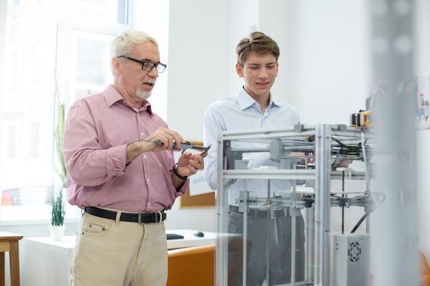 いつもの日。彼と彼のインターンが3dプリンターでモデルを作成している間、キャリパーを使用してモデルを測定する準備をしている楽しい年配の男性
