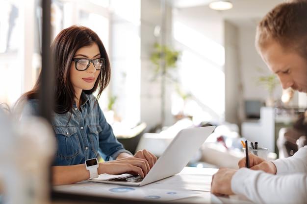 Обычные будни. серьезная трудолюбивая красивая женщина сидит за столом и печатает на ноутбуке во время работы в офисе