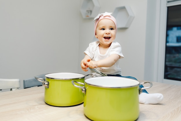 Ðâ¡ute baby girl in the kitchen playing with pans