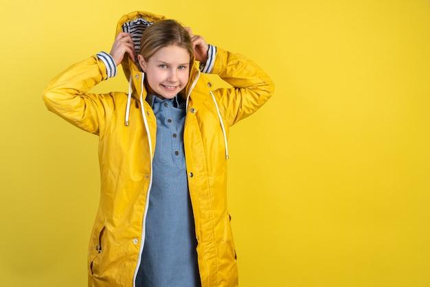 Ãâã'â¡ute little girl puts on the hood of her raincoat