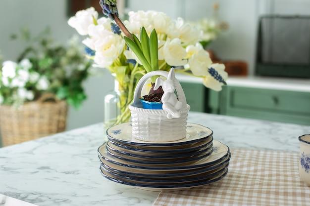Посуда, цветы и фарфоровые тарелки на обеденном столе на кухне