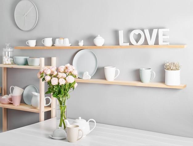調理器具、バラの花束、棚にマグカップ。キッチンの食器棚の料理。