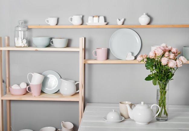 Utensils, bouquet of roses and mugs on shelf. dishes in cupboard in kitchen.