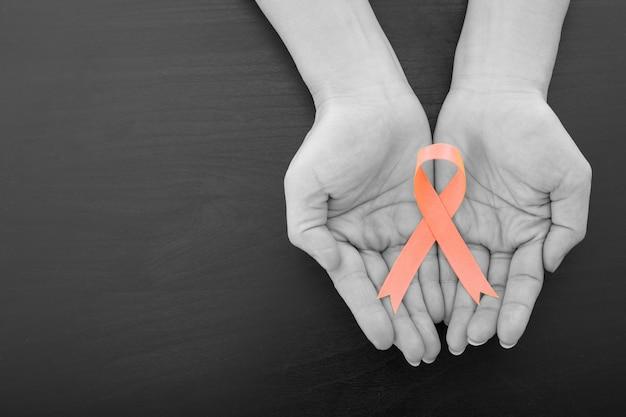 ヘルスケアの概念を示す必要がある女性が保持している子宮内膜がんのリボン。