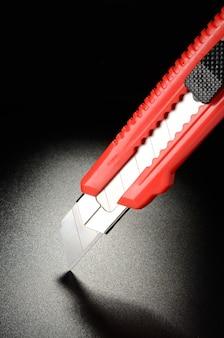 Универсальный нож, канцелярский нож на черной зернистой поверхности