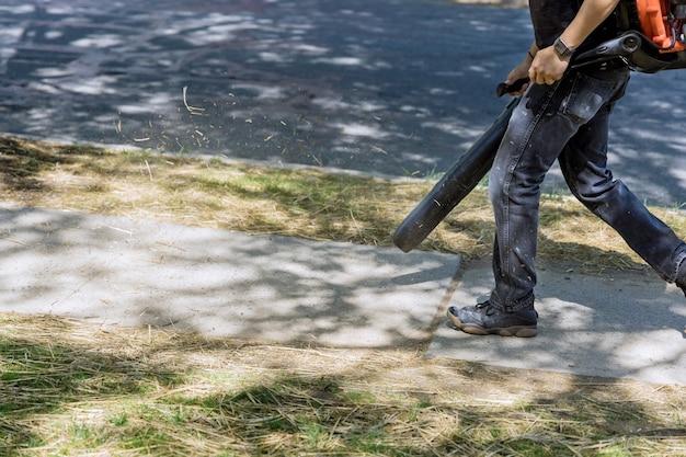 Работник коммунального предприятия мужского пола использует воздуходувку для удаления опавших листьев на сезонных работах.