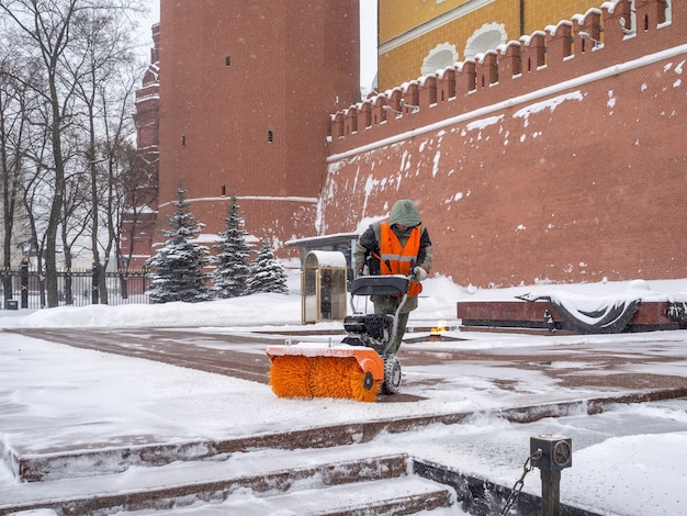 A utility worker cleans snow with a snowplow at the grave of the unknown soldier in the kremlin during a snowfall