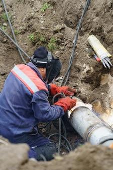 Коммунальный работник ремонтирует сломанную водопроводную канализационную трубу