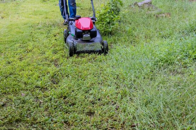 잔디 깎는 기계의 유틸리티 작업자 정원사는 잔디를 타고 잔디 깎는 기계를 절단