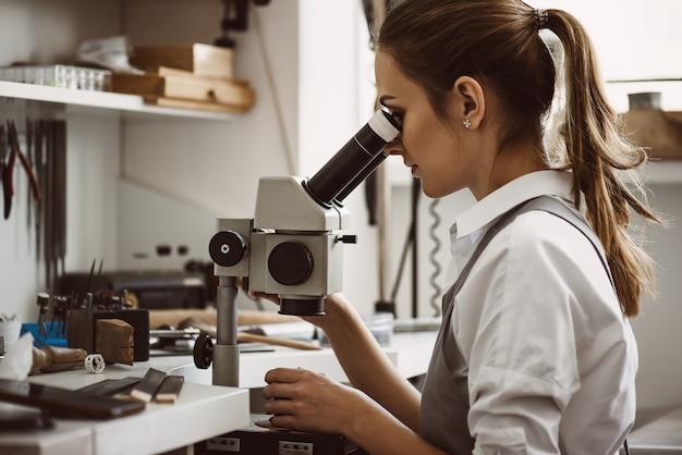 최고의 정밀도. 작업실에서 현미경을 통해 새 보석 제품을 보고 있는 여성 보석상의 초상화를 클로즈업하세요. 보석 제조 개념입니다. 주얼리 제작 워크숍. 마스터의 손