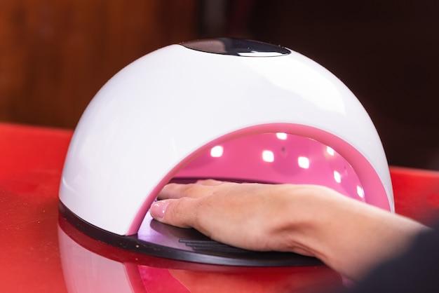 네일 살롱에서 uv 램프 젤 폴란드어 매니큐어 과정. 여자 손의 닫습니다.