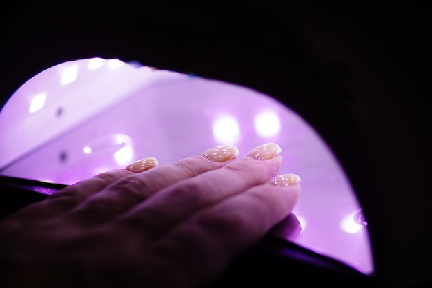 Uv lamp gel polish manicure process in a beauty salon