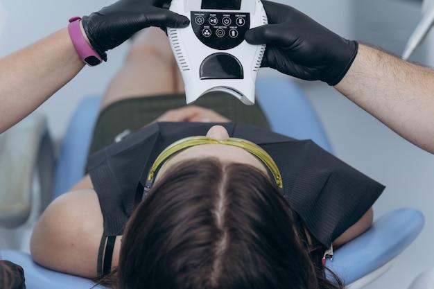 クリニックの歯科医で女性患者のクローズアップの肖像画。紫外線uvランプによる歯のホワイトニング手順