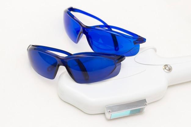 脱毛・脱毛用レーザー装置。と青い安全メガネ、uvプロテクション。脱毛、滑らかな肌、健康の概念。
