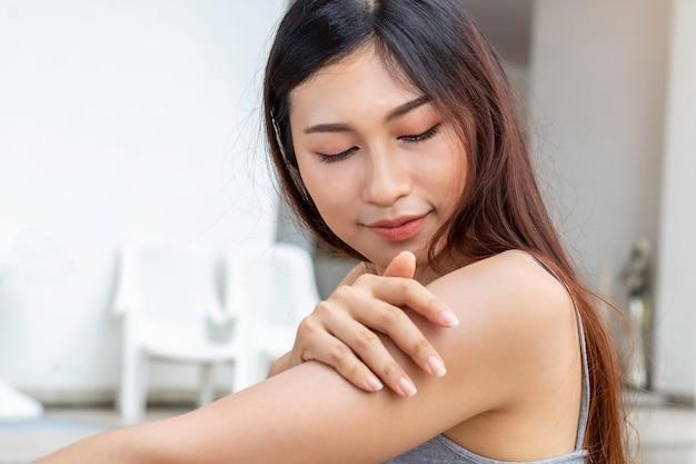 Молодая азиатская женщина при здоровая кожа прикладывая солнцезащитный крем uv защищает к плечу.