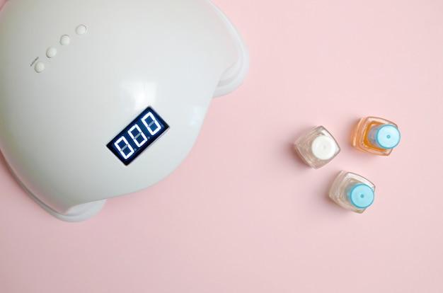 爪のuvダイオードランプライトとパステル調の背景にマニキュアとペディキュアの化粧品のマニキュアのセット