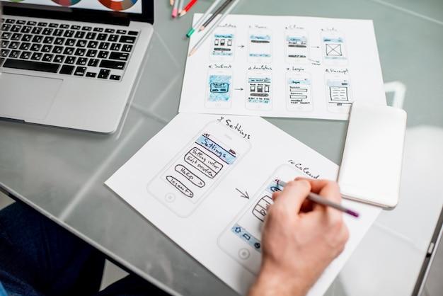 모바일 애플리케이션 작업을 하는 ux 디자이너는 사무실에서 스케치 드로잉을 경험합니다. 이미지 초점 없음 얼굴 없이 잘린 그림 없음