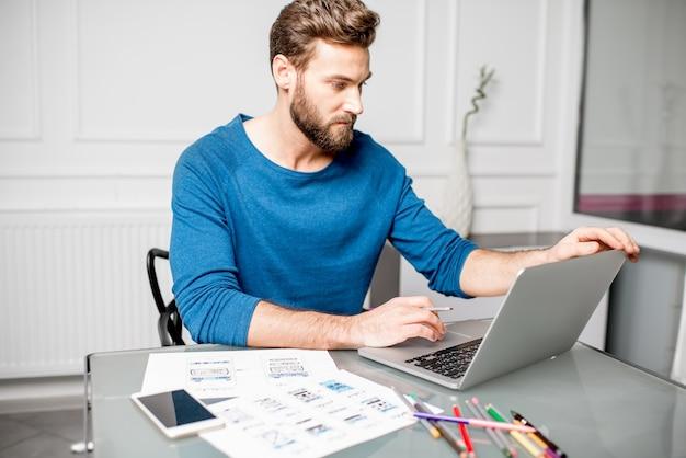 Ux-дизайнер, работающий над мобильным приложением, набрасывает чертежи в офисе.