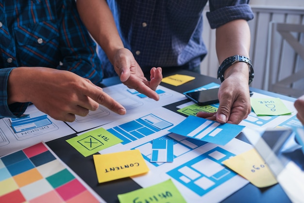 Ux/ui team of designers helping to create content and forms of mobile applications to make it easier for users to use.