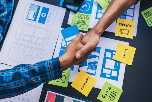 会議室で相談した後、ユーザーエクスペリエンスux / uiデザイナーのチームワークの同僚の握手。サポートプロジェクト。