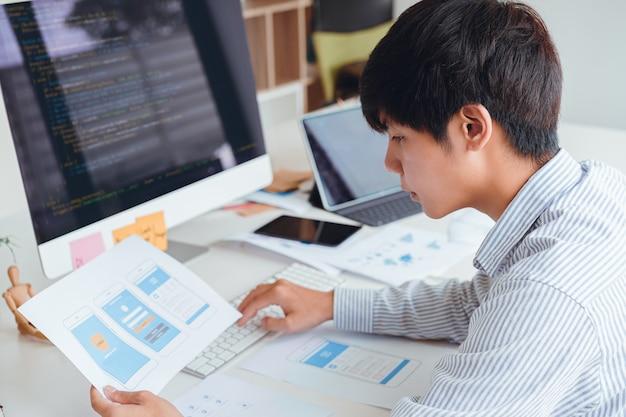 プロトタイプおよびワイヤフレームレイアウトからモバイルアプリケーションのプログラミングおよびコーディングを開発するスタートアップux uiフロントエンド設計者のクロップショット。モバイルアプリケーション開発者の職場の概念。