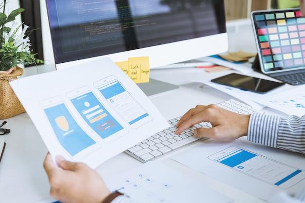 Обрезанный снимок стартап-дизайнеров ux ui, разрабатывающих мобильные приложения для программирования и кодирования на основе прототипа и макета каркаса концепция рабочего места разработчика мобильных приложений.