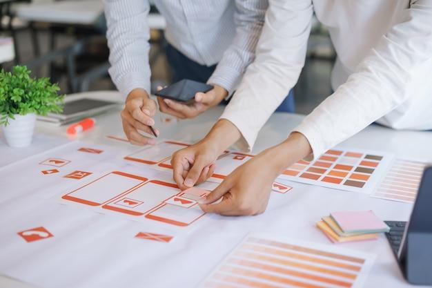 プロトタイプとワイヤーフレームレイアウトからモバイルアプリケーションを設計、開発している、創造的なux uiデザイナーチームのショットをトリミングしました。モバイルアプリケーション開発者の職場のコンセプトです。