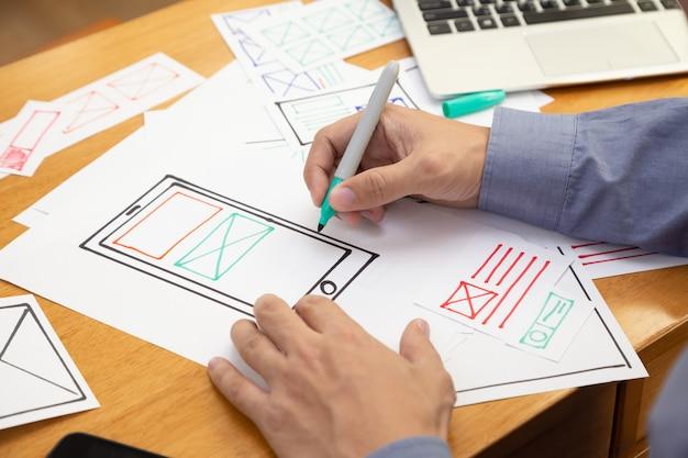 Uxグラフィックデザイナーのクリエイティブなスケッチとweb携帯電話用のプロトタイプワイヤフレームの計画