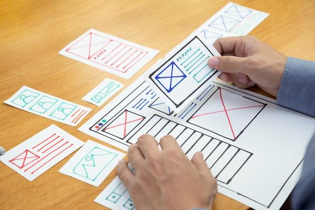 Uxグラフィックデザイナーの創造的なスケッチとweb携帯電話用のプロトタイプワイヤフレームの計画。アプリケーション開発とユーザーエクスペリエンスの概念